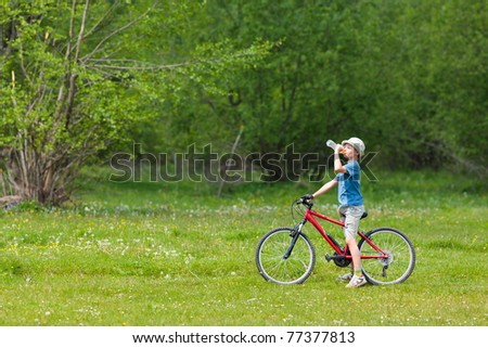 Boy with hat riding a bicycle on a grass field - stock photo