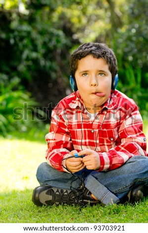 Boy with headphones listening to music at the park