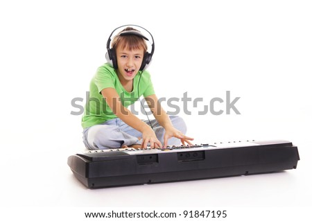 boy with headphones listening to music on a synthesizer - stock photo