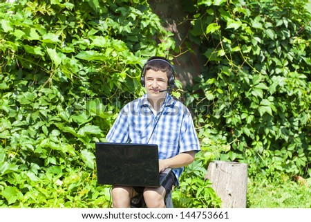 Boy with headphones, Mic and PC at outdoors - stock photo