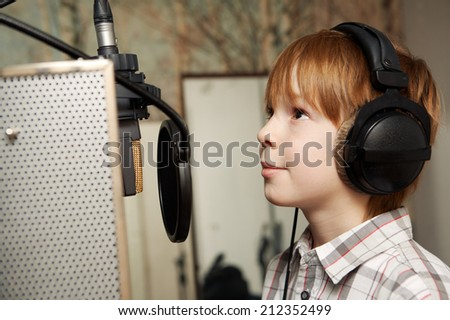 boy with headphones/redhead boy standing in front of a microphone with headphones - stock photo