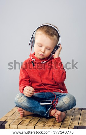Boy with headphones singing while listening to music - stock photo