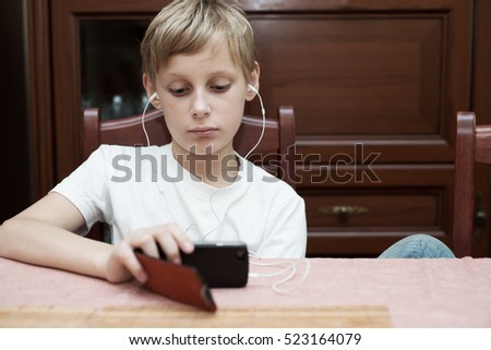 Boy with headphones sitting at the table and looking into the smartphone