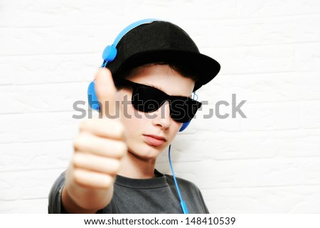 "Boy with headphones, sunglasses and cap in front of a white wall,, ""thumbs up"" - stock photo"