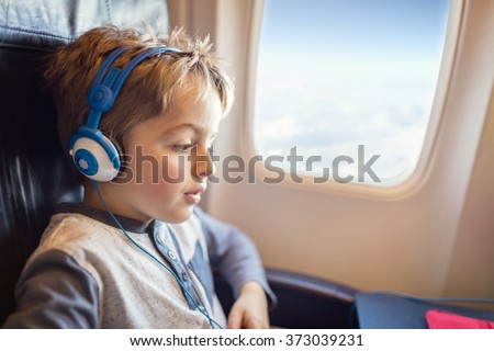 Boy with headphones watching and listening to in flight entertainment on board airplane - stock photo