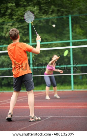 Boy with her mother play badminton on the playground, view from the back