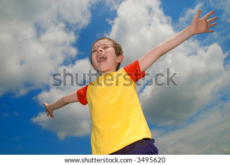 Boy with his arms wide open in front of a sky with clouds - stock photo