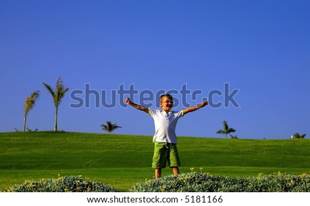 boy with his arms wide open on a golf camp - stock photo