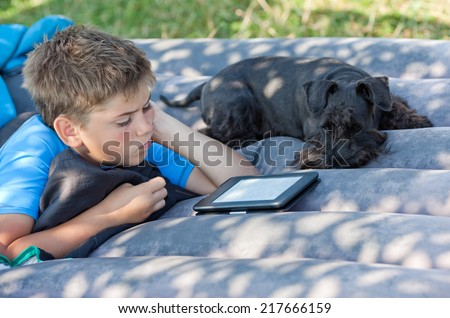 Boy with his dog are on mattress inflatable and read ebook - stock photo