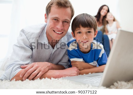Boy with his father using laptop together on the carpet - stock photo