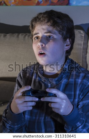 boy with joystick playing computer game at home. - stock photo