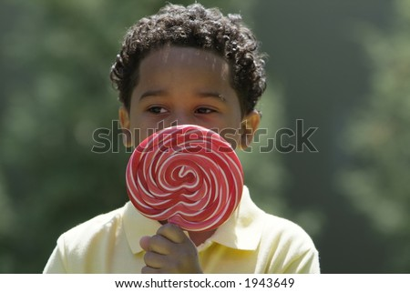 Boy with large lolipop in the park - stock photo