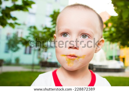 Boy with large lollipop in the park - stock photo