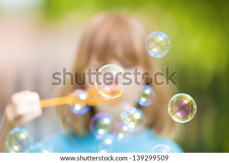 boy with long blond hair blowing soap bubbles - stock photo