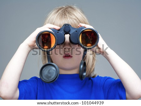 boy with long blond hair looking through binoculars - isolated on gray