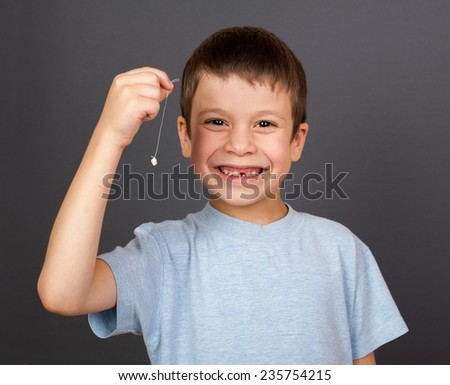 boy with lost tooth on a thread - stock photo