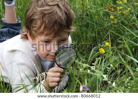 boy with magnifying glass outdoors - stock photo