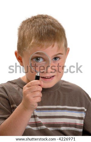 Boy with magnifying glass to his eye making eye bigger - stock photo