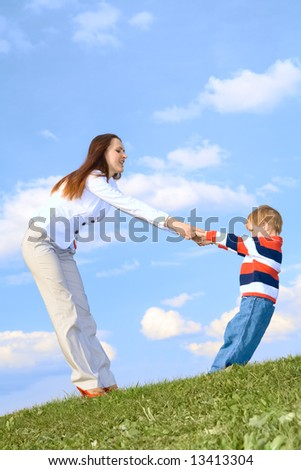Boy with mother playing on grass at blue sky background - stock photo