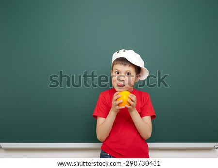 boy with orange fruit near the school board