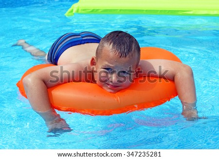 Boy with orange life ring in the swimming pool