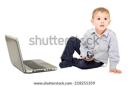 Boy with phone in hand sitting near laptop - stock photo