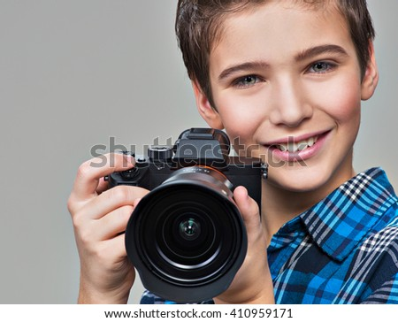 Boy with photo camera taking pictures. Portrait of the caucasian boy  with digital camera in hands - stock photo