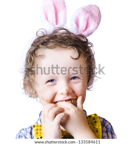 Boy with pink Easter bunny ears finishing off a chocolate egg on white background - stock photo