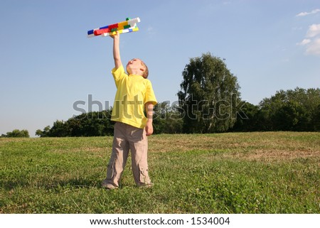 boy with plane on meadow - stock photo