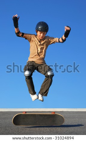 Boy with protective gear jumping high from a skateboard with blue background. - stock photo