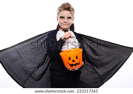 Boy with pumpkin basket dressed like vampire for Halloween party. Studio portrait isolated over white background   - stock photo
