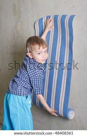 Boy with roll of wallpaper near wall. Flat repair - stock photo