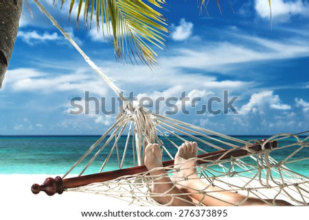 boy with sandy feet lying in a hammock at the beach - stock photo