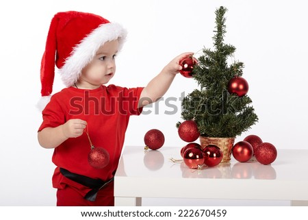 boy with Santa hat decorates christmas tree - stock photo