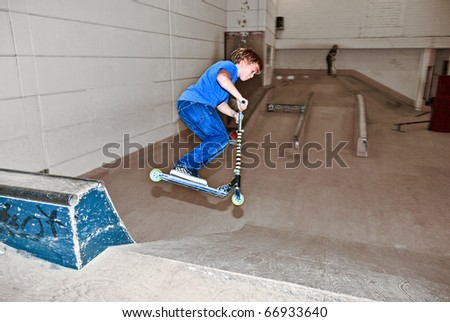 boy with scooter is going airborne in the skate hall - stock photo