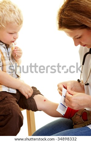 Boy with scratched knee at the pediatrist - stock photo