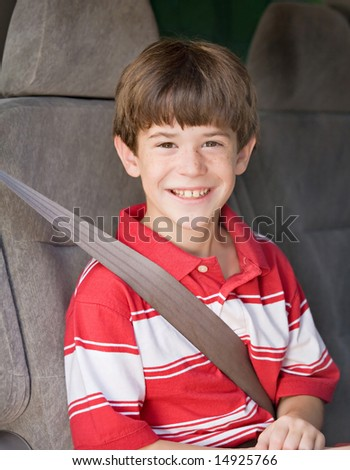 Boy With Seatbelt on Riding in Car - stock photo