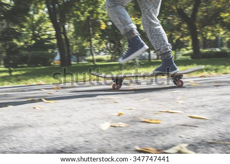 Boy with skateboard in the park. Autumn leaves - stock photo