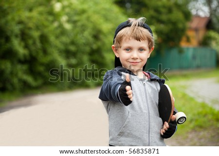 Boy with skateboard showing thumbs up sign outdoors - stock photo
