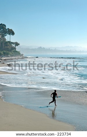 Boy with skimmer board running into the surf - stock photo