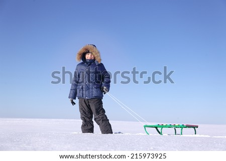 boy with sled on sky background - stock photo