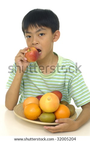 Boy with slices orange and plate of fruits