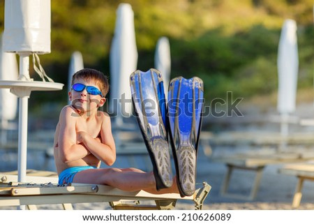 Boy with snorkeling equipment at tropical beach - stock photo