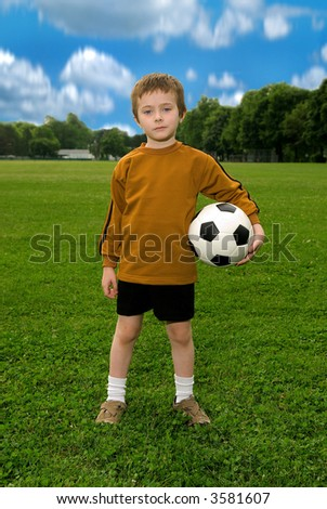 Boy with soccer ball against blue sky and green field