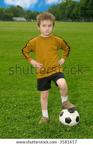 Boy with soccer ball against blue sky and green field - stock photo