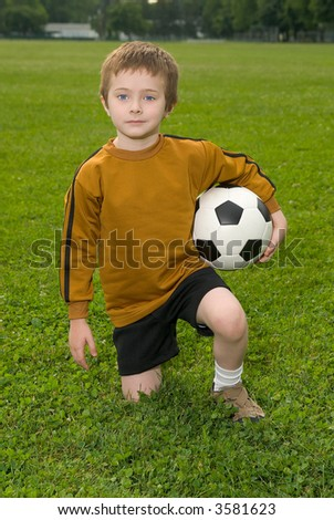 Boy with soccer ball kneeling on a green field - stock photo