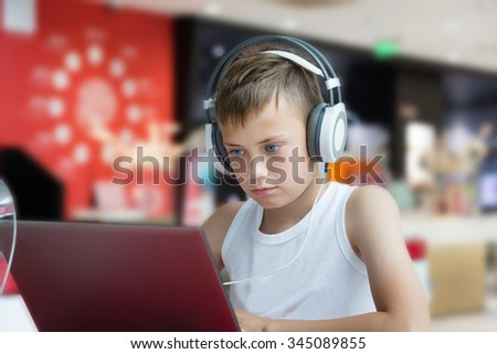 Boy with stylish headphones using a laptop - stock photo