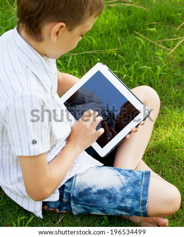 Boy with tablet outdoors. Child with pc computer