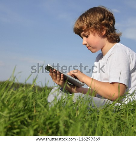 Boy with tablet pc outdoors - stock photo