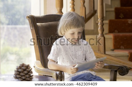 boy with tablet playing game or texting message - game, children, technology, internet communication and people concept